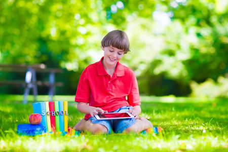 Happy smiling school boy, smart student, holding a white touch screen tablet computer relaxing on a school yard lawn reading books and having apple for lunch photo