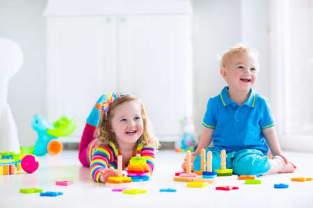 day care: Kids playing with wooden toys. Two children, cute toddler girl and funny baby boy, playing with wooden toy blocks, building towers at home or day care. Educational child toys for preschool and kindergarten. Stock Photo