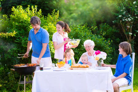 garden: Grill barbecue backyard party. Happy big family - young mother and father with kids, teen age son, cute toddler daughter and a little baby, enjoying BBQ lunch with grandmother eating grilled meat in the garden with salad and bread. Stock Photo