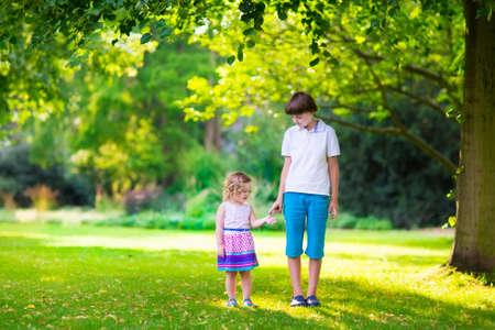 niños caminando: Niños jugando en un parque. Niños de la mano caminando en el bosque. Niña feliz lindo en un vestido de verano de colores y su hermano reír, adolescente activo, corriendo juntos, jugando en el parque en un día de verano hermosa