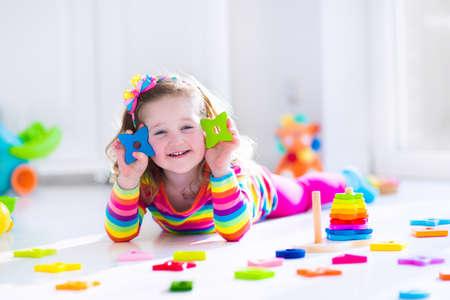 kinder: Niño que juega con los juguetes de madera en el preescolar. Muchacha linda del niño que se divierte con bloques de juguete, la construcción de una torre en la atención domiciliaria o de día. Juguete educativo para niños guardería o jardín de infancia. Foto de archivo