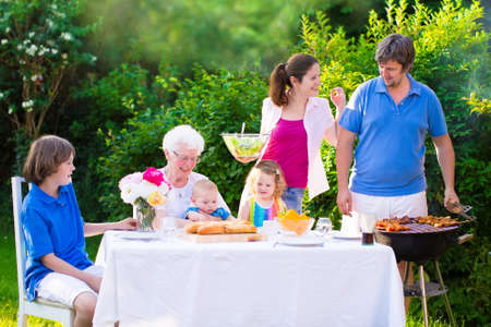garden barbecue: Grill barbecue backyard party. Happy big family - young mother and father with kids, teen age son, cute toddler daughter and a little baby, enjoying BBQ lunch with grandmother eating grilled meat in the garden with salad and bread. Stock Photo