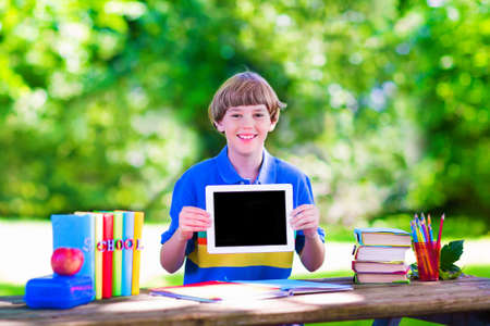school yard: Happy smiling school boy, smart student, holding a white touch screen tablet computer relaxing on a school yard lawn reading books , playing games and having apple for lunch, copy space for your text