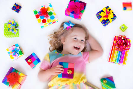 baby open present: Happy laughing little girl, adorable toddler in a colorful party dress, holding many birthday presents, opening boxes decorated with ribbon and bow, excited to celebrate a family holiday