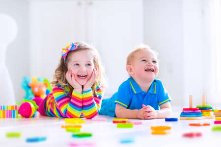 happy baby: Kids playing with wooden toys. Two children, cute toddler girl and funny baby boy, playing with wooden toy blocks, building towers at home or day care. Educational child toys for preschool and kindergarten. Stock Photo