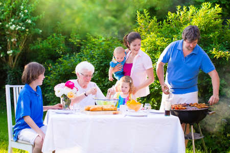 Grill barbecue backyard party. Happy big family - young mother and father with kids, teen age son, cute toddler daughter and a little baby, enjoying BBQ lunch with grandmother eating grilled meat in the garden with salad and bread. Stock Photo