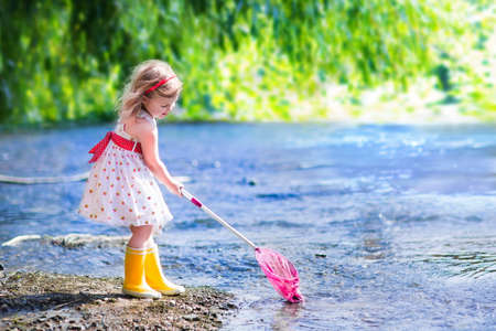 Child playing in a river. Cute little girl in a summer dress and rain boots catching fish and frog with a colorful net standing in water. Kids play outdoors. Young explorer and fisherman in wild nature.