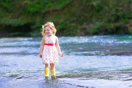 petite fille avec robe: Adorable petite fille bouclés bébé portant une robe jeu rouge et blanc au bord d'une rivière jeter des pierres dans l'eau sur une journée d'été chaude et ensoleillée