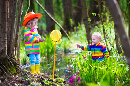 family with two children: Children playing outdoors. Two preschooler kids catching frog with colorful net. Little boy and girl fishing in a forest river in summer. Adventure kindergarten day trip into wild nature, young explorer hiking and watching animals.