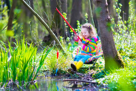 Child playing outdoors. Preschooler kid catching fish with red rod. Little girl fishing in forest river in summer. Adventure kindergarten day trip in wild nature, explorer hiking and watching animals. photo