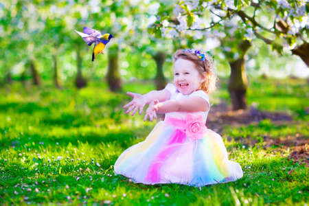 frutas divertidas: Ni�o que juega con un p�jaro. La ni�a feliz riendo en traje de hadas con alas que alimentan un loro en un jard�n de cerezo celebraci�n de una jaula de p�jaros. Ni�os que se divierten en la floraci�n huerto de frutales en primavera.