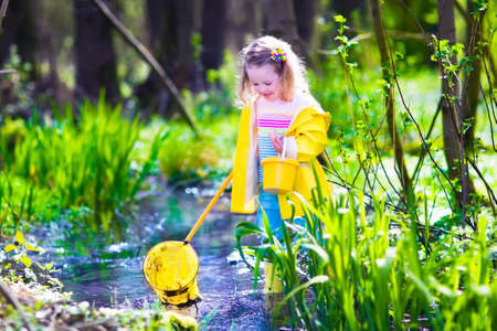 hunting: Child playing outdoors. Preschooler kid catching frog with colorful net. Little girl fishing in a forest river in summer. Adventure kindergarten day trip into wild nature, young explorer hiking and watching animals. Stock Photo