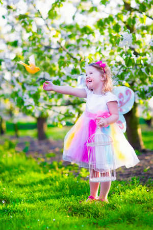 fairy garden: Child playing with a bird. Happy laughing little girl in fairy costume with wings feeding a pet parrot in a cherry tree garden holding a bird cage. Kids having fun in blooming fruit orchard in spring.