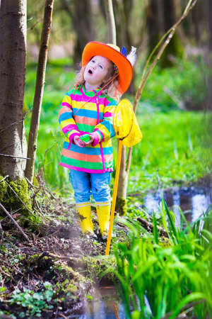 Child playing outdoors. Preschooler kid catching frog with colorful net. Little girl fishing in a forest river in summer. Adventure kindergarten day trip into wild nature, young explorer hiking and watching animals. photo