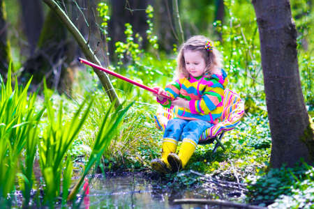 kindergarten: Child playing outdoors. Preschooler kid catching fish with red rod. Little girl fishing in a forest river in summer. Adventure kindergarten day trip into wild nature, explorer hiking and watching animals.