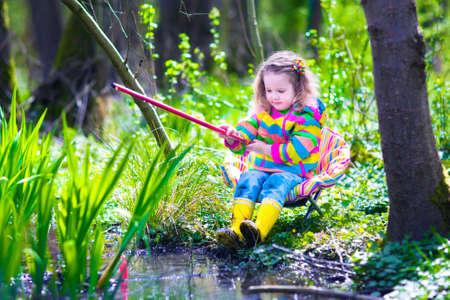 kinder: Ni�o que juega al aire libre. Ni�o en edad preescolar ni�o pescando con ca�a rojo. Pesca de la ni�a en un r�o del bosque en verano. Aventura kindergarten viaje de un d�a en la naturaleza salvaje, senderismo explorador y animales que miran.