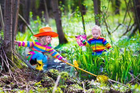 Children playing outdoors. Preschool kids catching frog with net. Boy and girl fishing in forest river. Adventure kindergarten day trip into wild nature, young explorer hiking and watching animals. photo
