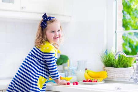 raspberry dress: Little girl preparing breakfast in white kitchen. Healthy food for children. Child drinking milk and eating fruit. Happy smiling preschooler kid enjoying morning meal, cereal, banana and strawberry.