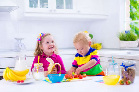 raspberry dress: Little girl and boy preparing breakfast in white kitchen. Healthy food for children. Child drinking milk and eating fruit. Happy smiling preschooler kids enjoying morning meal, cereal, banana and strawberry.