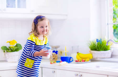 raspberry dress: Little girl preparing breakfast in a white kitchen. Healthy food for children. Child drinking milk and eating fruit. Happy smiling preschooler kid enjoying morning meal, cereal with banana and strawberry. Stock Photo