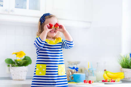 preparing food: Little girl preparing breakfast in white kitchen. Healthy food for children. Child drinking milk and eating fruit. Happy smiling preschooler kid enjoying morning meal, cereal, banana and strawberry.