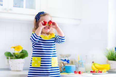 comiendo cereal: Niña que prepara el desayuno en la cocina blanca. Alimentos sanos para los niños. Niño beber leche y comer frutas. Feliz sonriente niño preescolar disfrutando de comida de la mañana, cereales, plátano y fresa.