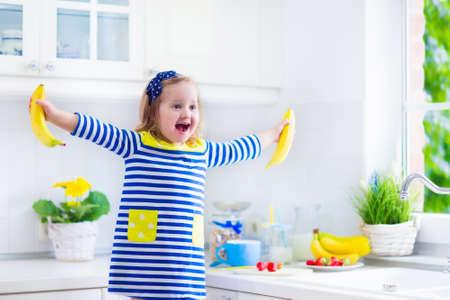 banane: Petite fille pr�parer le petit d�jeuner dans la cuisine blanc. Une alimentation saine pour les enfants. Enfant de boire du lait et manger des fruits. Sourire heureux d'�ge pr�scolaire enfant appr�ciant le repas du matin, des c�r�ales, de la banane et de fraise.