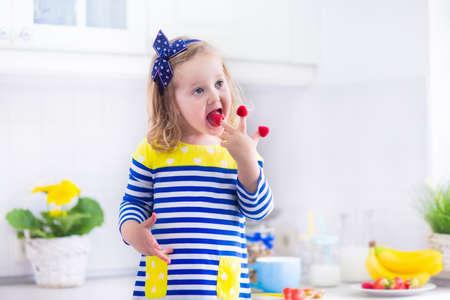 raspberry dress: Little girl preparing breakfast in white kitchen. Healthy food for children. Child drinking milk and eating fruit. Happy smiling preschooler kid enjoying morning meal, cereal, banana and raspberry. Stock Photo