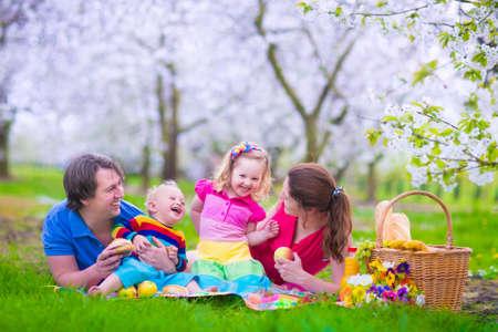 Jong gezin met kinderen met picknick buitenshuis. Ouders met twee kinderen ontspannen in een bloeiende zomertuin. Moeder, vader, meisje en jongetje eet broodje en fruit, sap drinken voor gezonde lunch in een park.