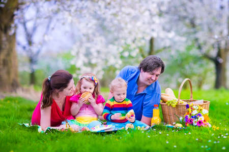 frutas divertidas: Familia joven con los niños que tienen comida campestre al aire libre. Los padres con dos niños a relajarse en un jardín de verano en flor. Madre, padre, niña y bebé comer bocadillo y fruta, jugo de bebida para el almuerzo saludable en un parque.