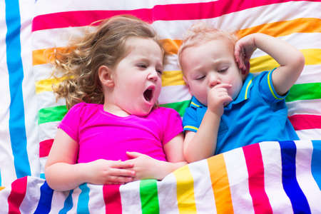 tired man: Two kids sleeping in bed under colorful blanket. Children relaxing in bedroom. Tired toddler girl and baby boy before bedtime. Rainbow textile bedding for nursery. Brother and sister play at home.