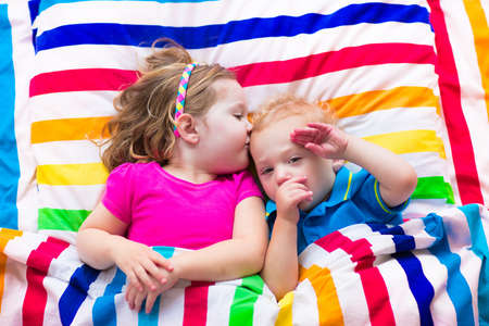 bedding: Two kids sleeping in bed under colorful blanket. Children relaxing in bedroom. Tired toddler girl and baby boy before bedtime. Rainbow textile bedding for nursery. Brother and sister play at home.