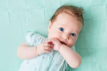 face of infant: Cute little baby girl on a knitted blanket. Children portrait. Kids bedding. Newborn child relaxing in bed. Adorable infant with blue eyes and dark curly hair.