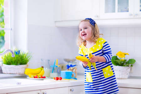raspberry dress: Little girl preparing breakfast in white kitchen. Healthy food for children. Child drinking milk and eating fruit. Happy smiling preschooler kid enjoying morning meal, cereal, banana and strawberry. Kids cooking.