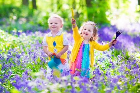 Niños jardinería. Niños que juegan al aire libre. Niña y niño, hermano y hermana, que trabaja en el jardín, plantando flores, regando cama de flores. Diversión de la familia en verano. Foto de archivo - 39792808