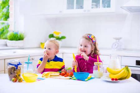 hombre comiendo: Niña y niño preparar el desayuno en la cocina blanca. Alimentos sanos para los niños. Niño beber leche y comer frutas. Preescolar feliz disfrutando de comida de la mañana, cereales, plátano y fresa. Niños cocinar.