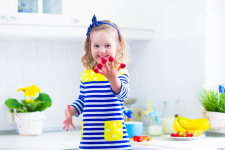 raspberry dress: Little girl preparing breakfast in kitchen. Healthy food for children. Child drinking milk and eating fruit. Happy preschooler kid enjoying morning meal, cereal, banana and raspberry. Kids cooking. Stock Photo