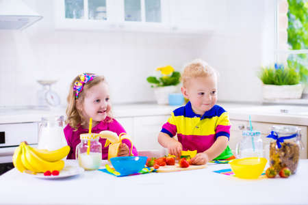 Little girl and boy preparing breakfast in kitchen. Healthy food for children. Child drinking milk and eating fruit. Happy smiling preschooler kids enjoy morning meal, cereal, banana and strawberry. Kids cooking. Stock Photo