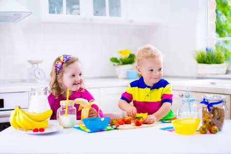 Meisje en jongen voorbereiding van het ontbijt in de keuken. Gezonde voeding voor kinderen. Kind het drinken van melk en het eten van fruit. Happy lachende peuter kinderen genieten ochtendmaaltijd, granen, banaan en aardbei. Kinderen koken. Stockfoto - 39792978