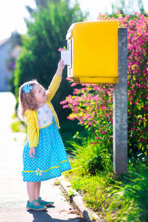 Little girl with an envelope at post office. Child sending letter. Kid throwing card into a mail box. Postal service in Germany, Europe. Delivery and shipment at outdoor mailbox. Stock Photo