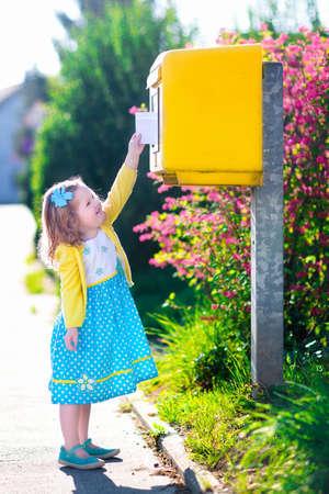 buzon: Niña con un sobre en la oficina de correos. Niño de enviar la carta. Kid lanzar tarjeta en un buzón de correo electrónico. Servicio postal en Alemania, Europa. Entrega y envío al buzón al aire libre. Foto de archivo