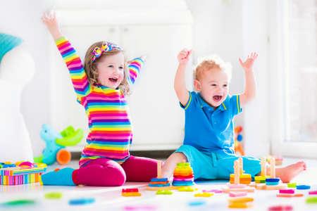 radost: Děti si hrají s dřevěnými hračkami. Dvě děti, roztomilý batole dívka a vtipné chlapeček, hraje s dřevěnými hračkami bloky, budování věže doma nebo denní péče. Vzdělávací dětské hračky pro předškolní a mateřské školy. Reklamní fotografie