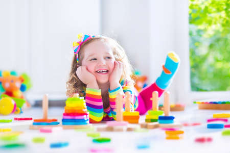 messy kids: Child playing with wooden toys at preschool. Cute toddler girl having fun with toy blocks, building a tower at home or day care. Educational kids toy for nursery or kindergarten.