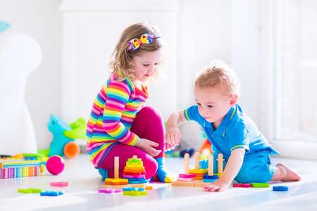 乳幼児: 木のおもちゃで遊ぶ子供たち。2 人の子供、かわいい幼児の女の子、面白い男の子は、おもちゃのブロックと自宅の塔を構築またはデイケアで遊んで。保育園と幼