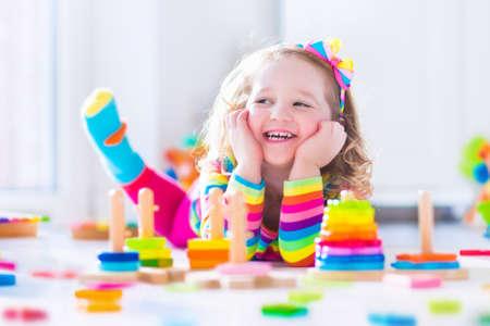 幼稚園で木のおもちゃと遊ぶ子供。かわいい幼児の女の子は、おもちゃのブロックと建物は自宅の塔またはデイ ・ ケアを楽しんでします。保育園や