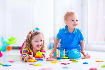 Niños jugando con los juguetes de madera. Dos niños, linda muchacha del niño y del muchacho divertido del bebé, jugando con bloques de juguete, la construcción de torres en la atención domiciliaria o días. Los niños juguetes educativos para preescolar y jardín de infantes.