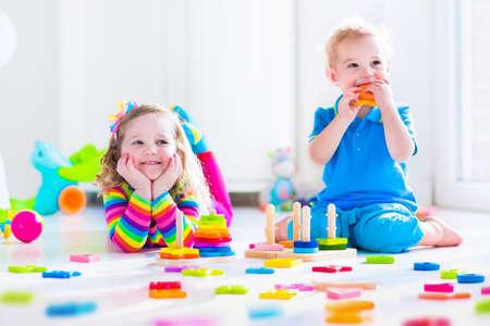 木のおもちゃで遊ぶ子供たち。2 人の子供、かわいい幼児の女の子、おもちゃのブロックは、自宅の塔を構築またはデイケアと一緒に遊んで面白い赤