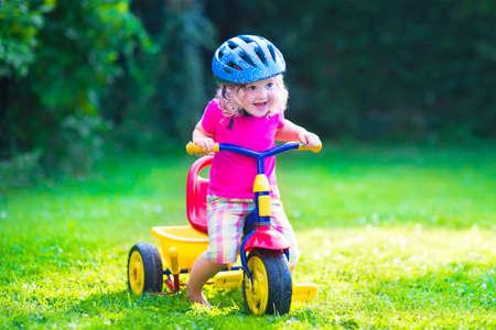 kinder spielen: Kinder mit dem Fahrrad. Kinder genießen eine Fahrradtour. Vorschüler kleine Mädchen Spaß im Freien. Aktive Kleinkinder spielen im Garten. Sommerspaß in einem Park. Kind trägt Schutzhelm.
