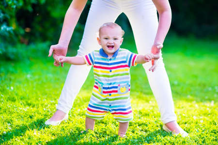 Baby boy making his first steps. Mother holding her child. Kid walking on a lawn in a sunny summer garden. Kids learning to walk. Zdjęcie Seryjne