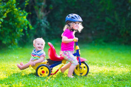 tricycle: Children riding a bike. Kids enjoying a bicycle ride. Little preschooler girl and baby boy, brother and sister, having fun outdoors. Active toddlers play in the garden.